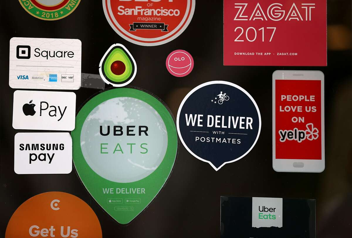 SAN FRANCISCO, CALIFORNIA - JULY 06: A Postmates sticker is displayed next to an Uber Eats sticker on the window of a restaurant on July 06, 2020 in San Francisco, California. Uber announced plans to buy restaurant delivery company Postmates for $2.65 billion in an all-stock deal. (Photo by Justin Sullivan/Getty Images)