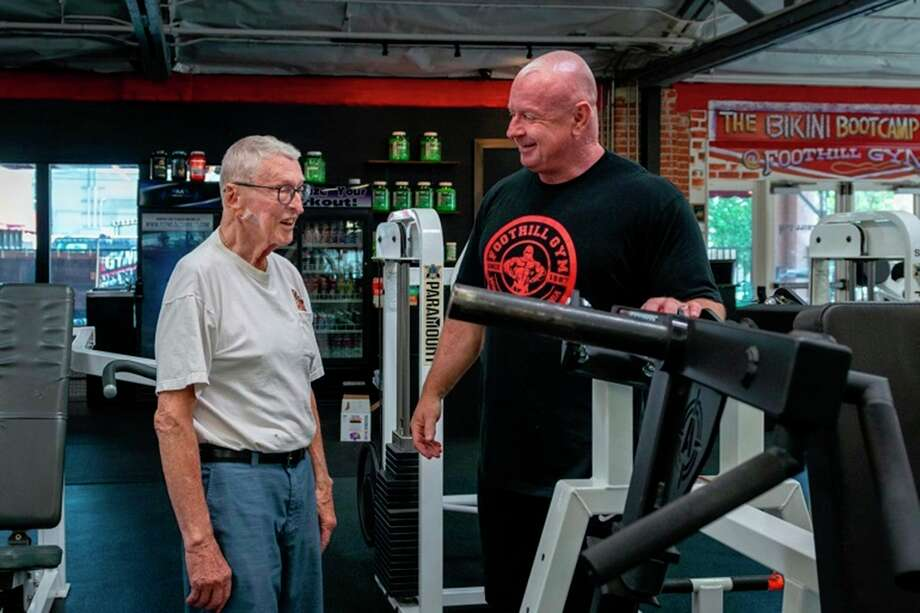 """Art Ballard takes a break between sets to chat with Foothill Gym owner Brian Whelan on June 13, 2020. For Ballard, the benefits of the gym are twofold. """"It's the health factor and the social aspect,"""" he says. """"Everybody there is so positive. It makes my day worthwhile."""" (Heidi de Marco/TNS) / Kaiser Health News"""