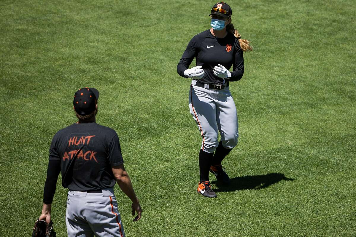 Coach Alyssa Nakken, right, speaks with Hunter Pence #8 of the San Francisco Giants during summer training camp at Oracle Park in San Francisco, Calif. on Monday, July 6, 2020.
