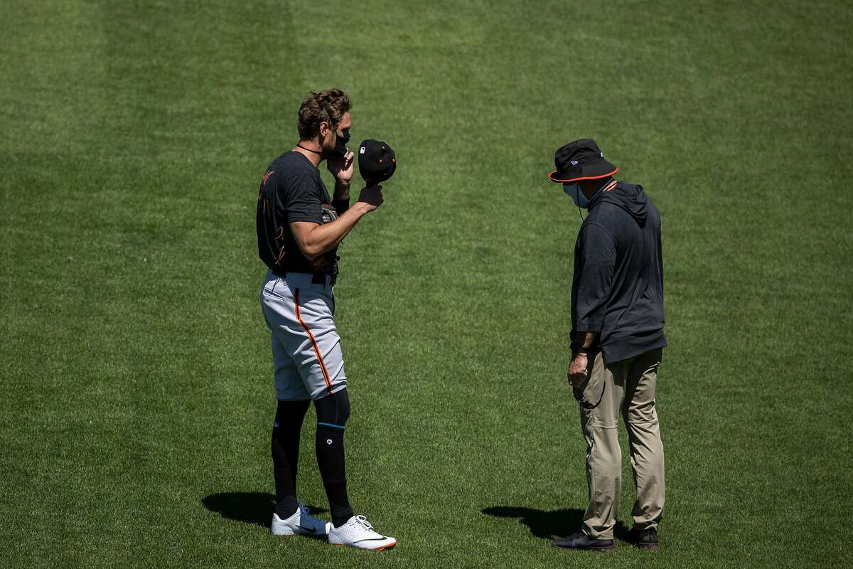 Hunter Pence #8 of the San Francisco Giants adjusts his mask as he speaks with a member of the training staff during summer training camp at Oracle Park in San Francisco, Calif. on Monday, July 6, 2020.