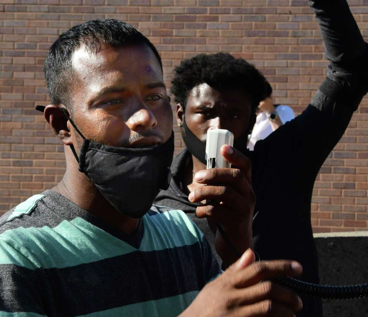 Yugeshwar Gaindarpersaud speaks with a megaphone as protesters express their anger outside Schenectady Police Headquarters after a police officer was video-recorded allegedly kneeling on his neck while trying to apprehend him on Brandywine Avenue on Monday, July 6, 2020 in Schenectady, N.Y. (Lori Van Buren/Times Union)
