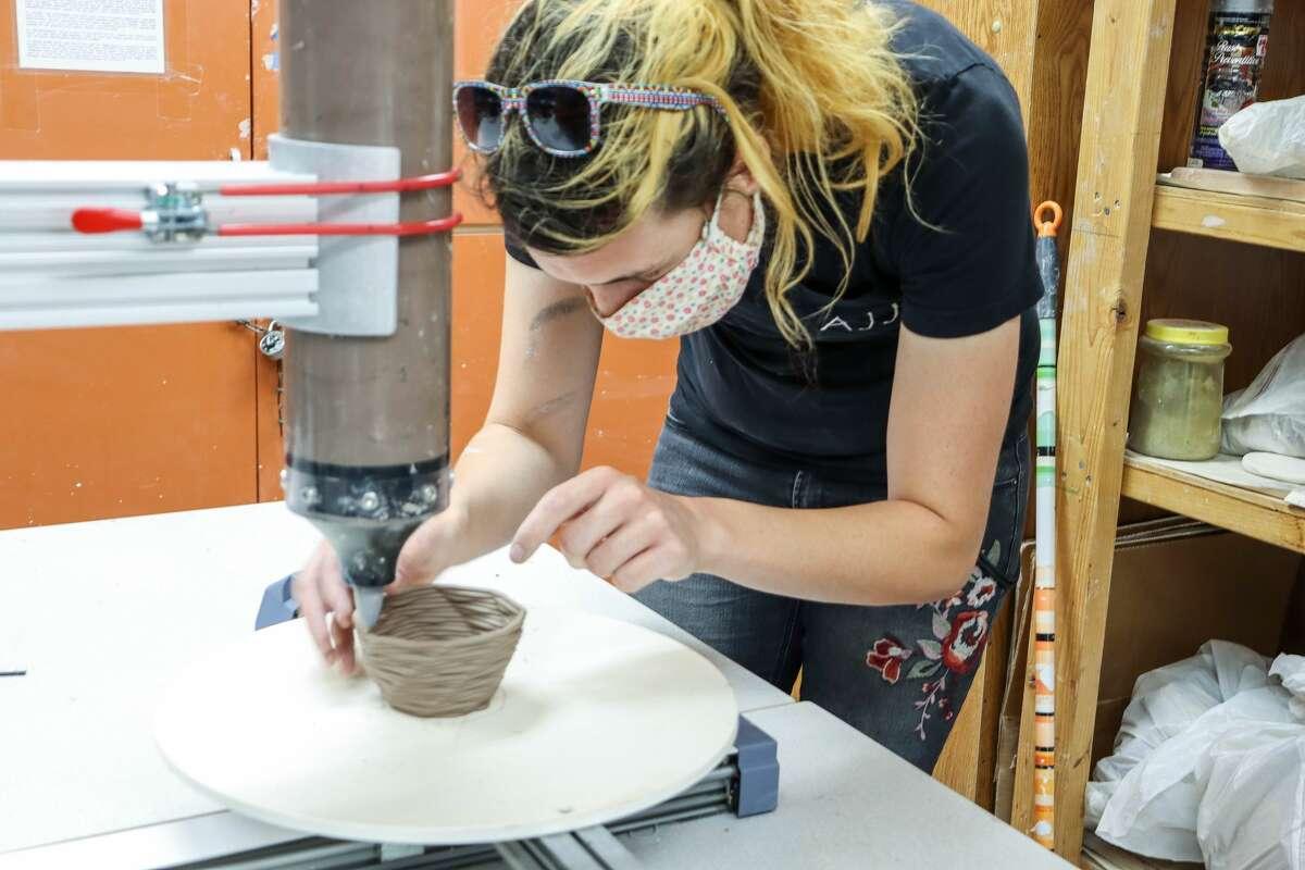 Jayce Barrett creates pottery using Midland College's new GlowForge laser cutter/etcher.