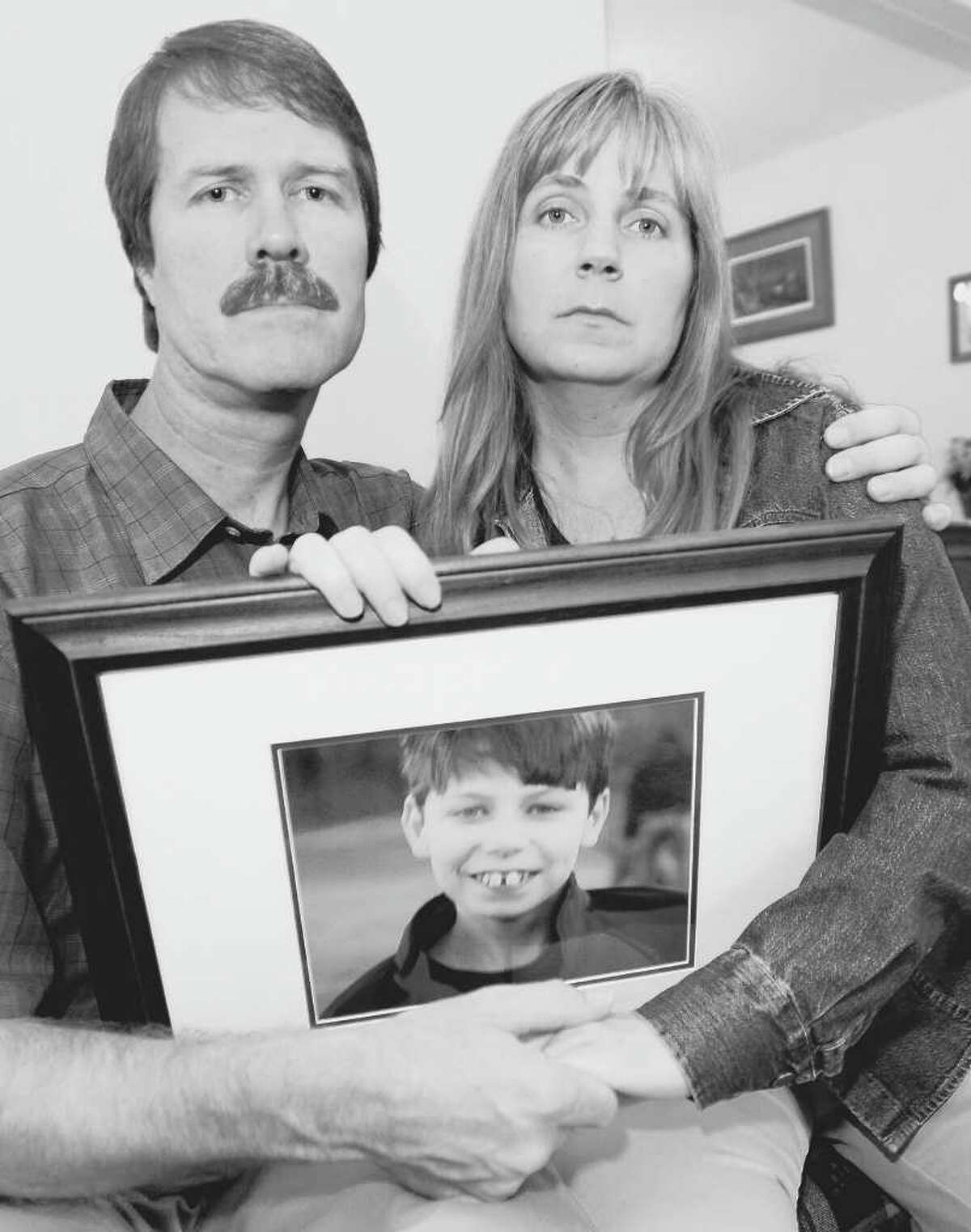 Michael and Lisa Carey hold a photo of their child, Jonathan Carey. They sued over his private care and settled. The 13-year-old autistic youth later died while under state care in Niskayuna. (LUANNE M. FERRIS/TIMES UNION archive)