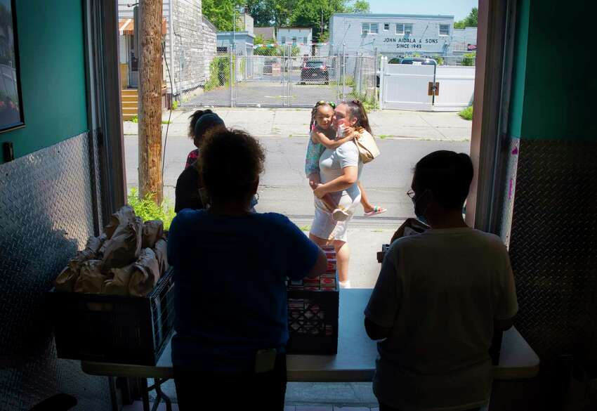Alixandra Pimentel, background center, gets a hug from a little girl after the girl received her lunch during the first day of the Victory Church summer feeding program at the JC Club on Monday, July 6, 2020, in Albany, N.Y. Maggie Dennis, foreground left, and Sarah Fountain, foreground right, distribute lunches to other children. The lunch program will run Monday through Friday from noon to 1:30pm. The church also runs a breakfast feeding program at 10:00 am Monday through Friday. (Paul Buckowski/Times Union)