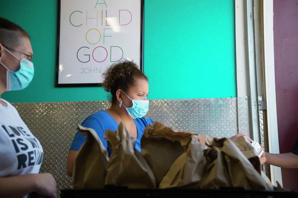 Sarah Fountain, left, and Maggie Dennis, right, distribute lunches to children during the first day of the Victory Church summer feeding program at the JC Club on Monday, July 6, 2020, in Albany, N.Y. The lunch program will run Monday through Friday from noon to 1:30pm. The church also runs a breakfast feeding program at 10:00 am Monday through Friday. (Paul Buckowski/Times Union)