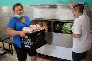 Maggie Dennis, left, and Sarah Fountain pull out milk from a cooler at they get lunches ready during the first day of the Victory Church summer feeding program at the JC Club on Monday, July 6, 2020, in Albany, N.Y. The lunch program will run Monday through Friday from noon to 1:30pm. The church also runs a breakfast feeding program at 10:00 am Monday through Friday.   (Paul Buckowski/Times Union)