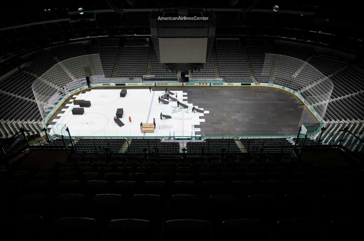 FILE - In this March 12, 2020, file photo, crews cover the ice at American Airlines Center in Dallas, home of the Dallas Stars hockey team, after the NHL season was put on hold due to the coronavirus.A Deputy Commissioner Bill Daly told The Associated Press on Sunday, July 5, that the NHL and NHL Playersa€™ Association have agreed on protocols to resume the season. Daly said the sides are still negotiating a collective bargaining agreement extension. A CBA extension is still crucial to the process. (Ashley Landis/The Dallas Morning News via AP, File)