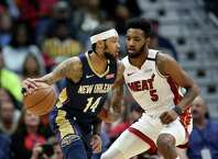 New Orleans Pelicans forward Brandon Ingram (14) dribbles as Miami Heat forward Derrick Jones Jr. (5) defends during the first half of an NBA basketball game in New Orleans, Friday, March 6, 2020. (AP Photo/Rusty Costanza)