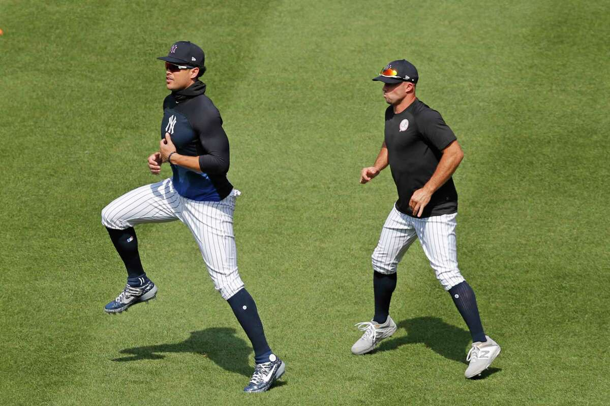 New York Yankees' Brett Gardner, right, and designated hitter Giancarlo Stanton go through an exercise drill during a baseball summer training camp workout Sunday, July 5, 2020, at Yankee Stadium in New York. (AP Photo/Kathy Willens)