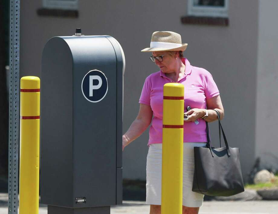 Greenwich's Carolyn Zonino pays for parking in the Liberty Way parking lot in downtown Greenwich on Monday, when many months of free town parking ended as meters and town lots became enforced again. Photo: Tyler Sizemore / Hearst Connecticut Media / Greenwich Time