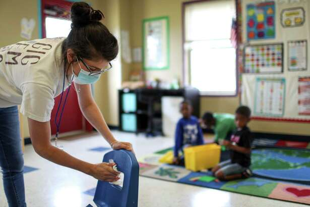 Julia Revelli, a lead teacher for the after school program at Little Academy of Humble, cleans her classroom Tuesday, June 23, 2020, at the school in Humble, Texas. At least 894 staff members and 441 children at Texas's child care centers have tested positive for coronavirus, according to the state's department of public health.