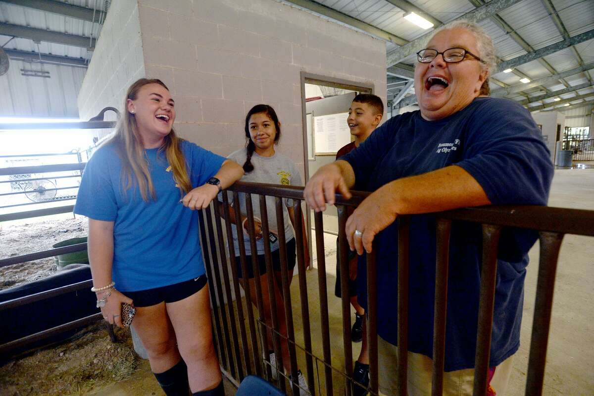 From left, Annabelle Benton and Kelly and Javi Velazquez joke with instructor Stephanie Hoppe at the BISD Agriculture Department's barn Monday. While certain aspects of the curriculum could move online, as had all coursework in the wake of COVID-19 school closure, the ag program was unique. Students in the FFA have animals, whose care cannot be done virtually. Feeding, cleaning, mucking stalls and cages and walking the animals are daily chores, and department head Stephanie Hoppe had to devise a plan to allow students to tend to their animals while adhering to safety guidelines. And the number of animals needing care was greater than normal, as the closure of the South Texas State Fair and Houston Rodeo meant animals that normally would have been shown and later auctioned, were now back at the barn. Hoppe and students hustled to find buyers, only to be met with a wait list for packing houses. The cost of feeding those animals in the meanwhile fell to students, some of whom broke just above even by the time their animals left the barn. Photo taken Monday, June 22, 2020 Kim Brent/The Enterprise
