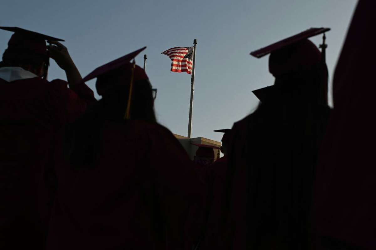 A US flag flies above a building as students earning degrees at Pasadena City College participate in the graduation ceremony, June 14, 2019, in Pasadena, California.