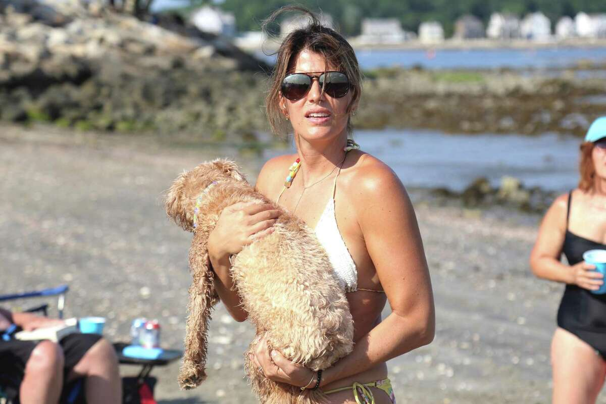 Gia Wright of Westport and her dog Nickel visit on the eastern end of Compo Beach, just over the jetty, on Saturday, July 4, 2020, in Westport, Conn.