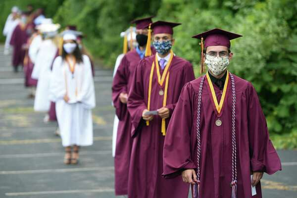 Graduates line up socially distant with face masks before crossing the stage and receiving their diplomas at the Sheehan High School graduation ceremony in the parking lot of the Toyota Oakdale Theatre in Wallingford on July 6, 2020.