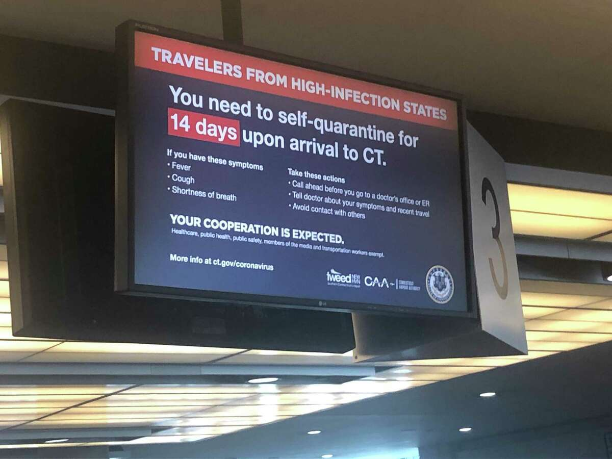 A sign at Bradley International Airport warns travelers on June 25, 2020 of a mandatory 14-day quarantine imposed by the governors of New York, Connecticut and New Jersey.