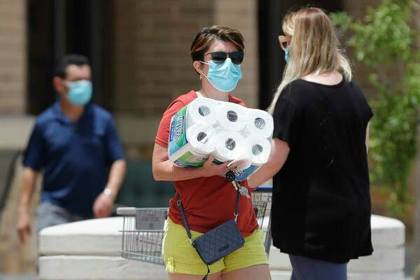 Shoppers wear face masks after Gov. Greg Abbott's statewide face covering order went into effect at noon, Friday, July 3, 2020, in Conroe. Abbott's order, which affects counties with more than 20 coronavirus cases, was spurred by the state's rising cases of COVID-19 in an effort to slow the virus' spread.