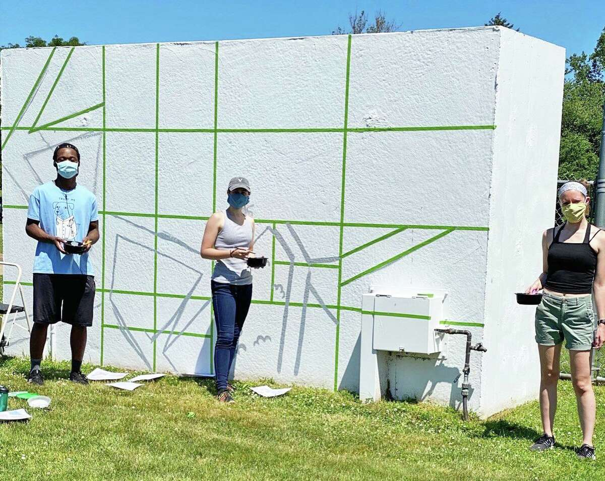 Cromwell Creative District and Cromwell High School's National Arts Honor Society have teamed up to showcase the new dugout murals at Pierson Park. From left, Kaya Anderson, Abby Darius, and coordinator Erin Trousdale grid out one of the murals.
