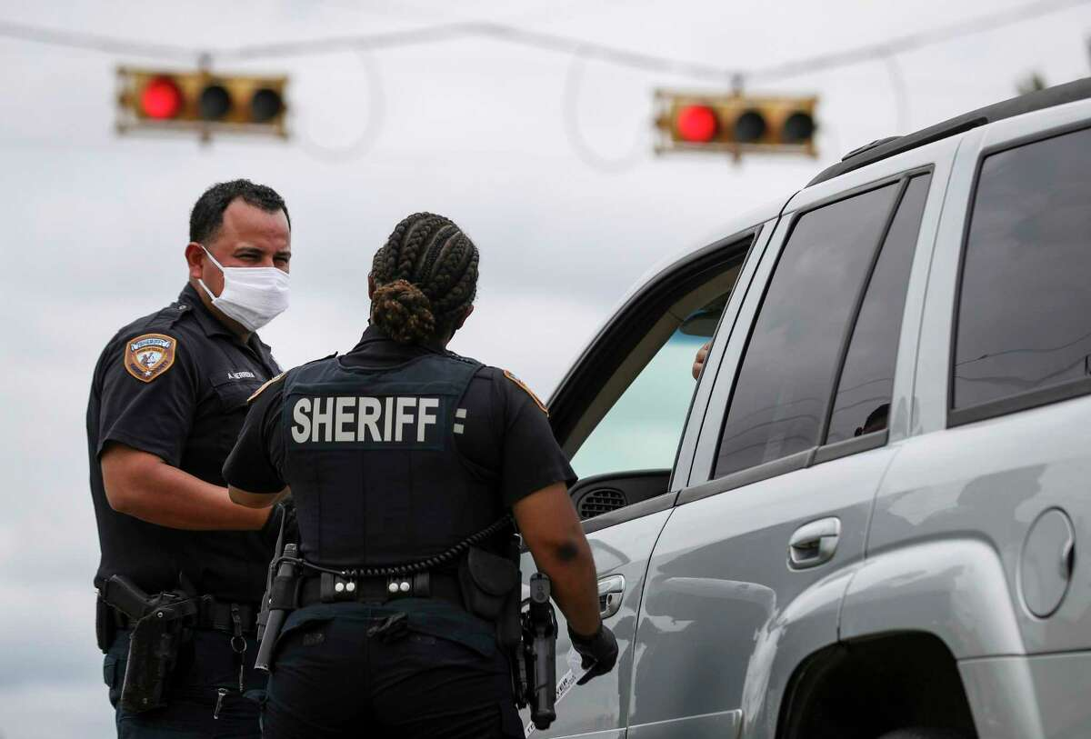 Harris County Sheriff's deputies Aaron Herrera, left, Nakeitha Dussette speak to a woman after Dussette initiated a traffic stop Wednesday, June 24, 2020, at the intersection of Bellaire Boulevard and Metro Boulevard in Houston.