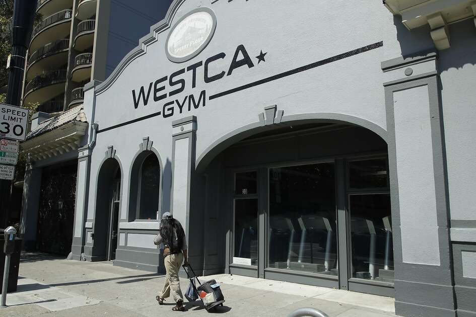 A person walks past the closed Westca Gym on Monday, July 6, 2020, in San Jose, Calif. The Independence Day weekend saw one of Santa Clara County's largest increases in COVID-19 cases to date, which came as the state of California denied the county's application for further reopening of businesses and activities. (AP Photo/Ben Margot)
