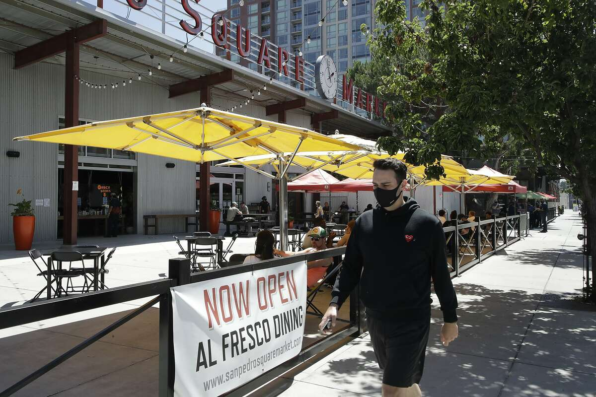 A masked man walks past outdoor diners at San Pedro Square on Monday, July 6, 2020, in San Jose, Calif. The Independence Day weekend saw one of Santa Clara County's largest increases in COVID-19 cases to date, which came as the state of California denied the county's application for further reopening of businesses and activities.