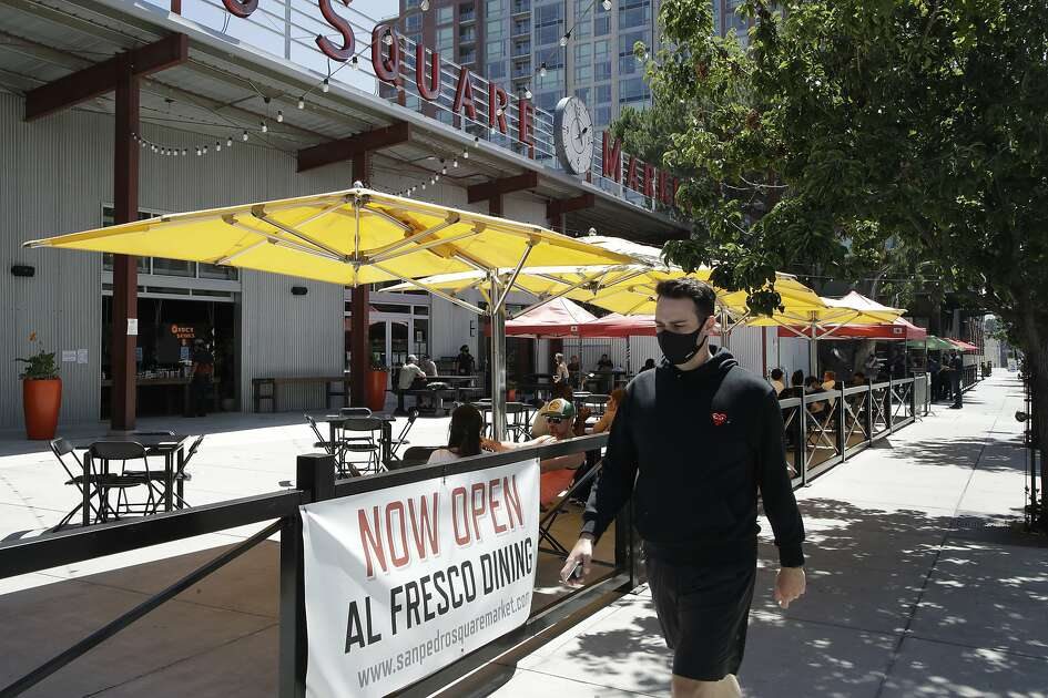 A masked man walks past outdoor diners at San Pedro Square on Monday, July 6, 2020, in San Jose, Calif. The Independence Day weekend saw one of Santa Clara County's largest increases in COVID-19 cases to date, which came as the state of California denied the county's application for further reopening of businesses and activities. (AP Photo/Ben Margot)