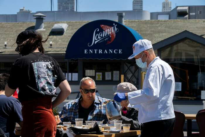 People eat at the outdoor seating area of Scoma's Restaurant on Tuesday, June 30, 2020, in San Francisco, Calif. Businesses along the Fisherman�s Wharf and Pier 39 are reportedly operating at around 20% the usual amount and struggling without the usual massive daily flood of tourists, amid the coronavirus pandemic.