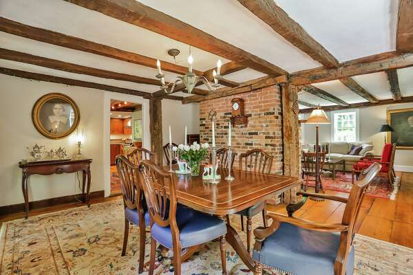 The banquet-sized formal dining room features exposed posts and beams and wide-board flooring.