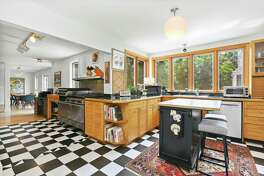 In the kitchen there is a black and white tile floor, ample counter space, built-in hutch with glass-front doors, and pantry.