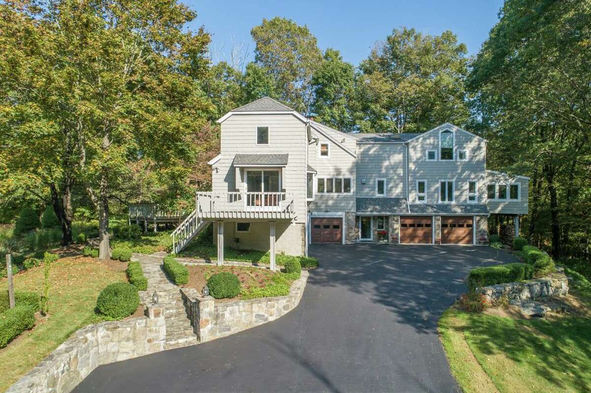 """The gray contemporary colonial house at 241 Maple Road in Easton sits on a 1.6-acre level and gently sloping lightly wooded property.   This is definitely the home for the athletic and the outdoorsy family. A multi-level stone terrace and two decks extend the living space to the back, side and even front yards where there are ornamental trees, fruit trees, perennial plantings, and a fenced-in vegetable garden. The acreage of the preserved open space hints at the privacy that this house enjoys, yet it is not more than a few minutes to the centers of Easton and Monroe, in opposite directions. """"Very private yet convenient to shopping (and dining) in Monroe and Route 25,"""" the listing agent said. Travel down Maple Road Extension and the long driveway to access this house, which is set well back from the road on its lightly wooded property. The driveway opens up in front of the three attached, under-house vehicle bays, providing additional parking for guests."""