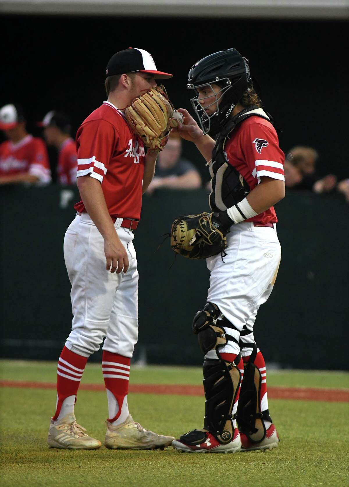Huffman pitcher Noah Zamora, left, gets the baseball and some words of encouragement from his catcher Grant O'Neal during the bottom of the fourth inning in Game One of their Region IV-4A Semi-Final Playoff Series at Madisonville High School on May 23, 2019.