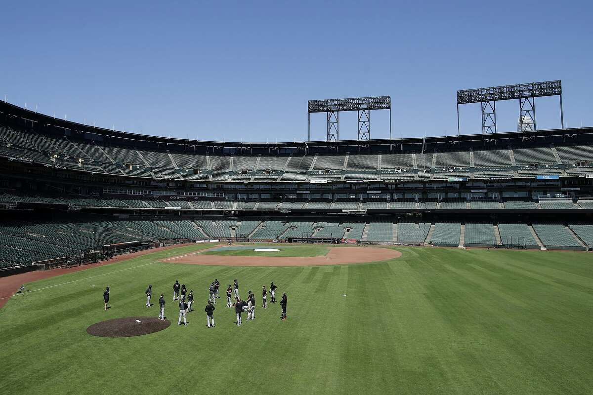 San Francisco Giants gather in the outfield at Oracle Park during a baseball practice in San Francisco, Sunday, July 5, 2020.