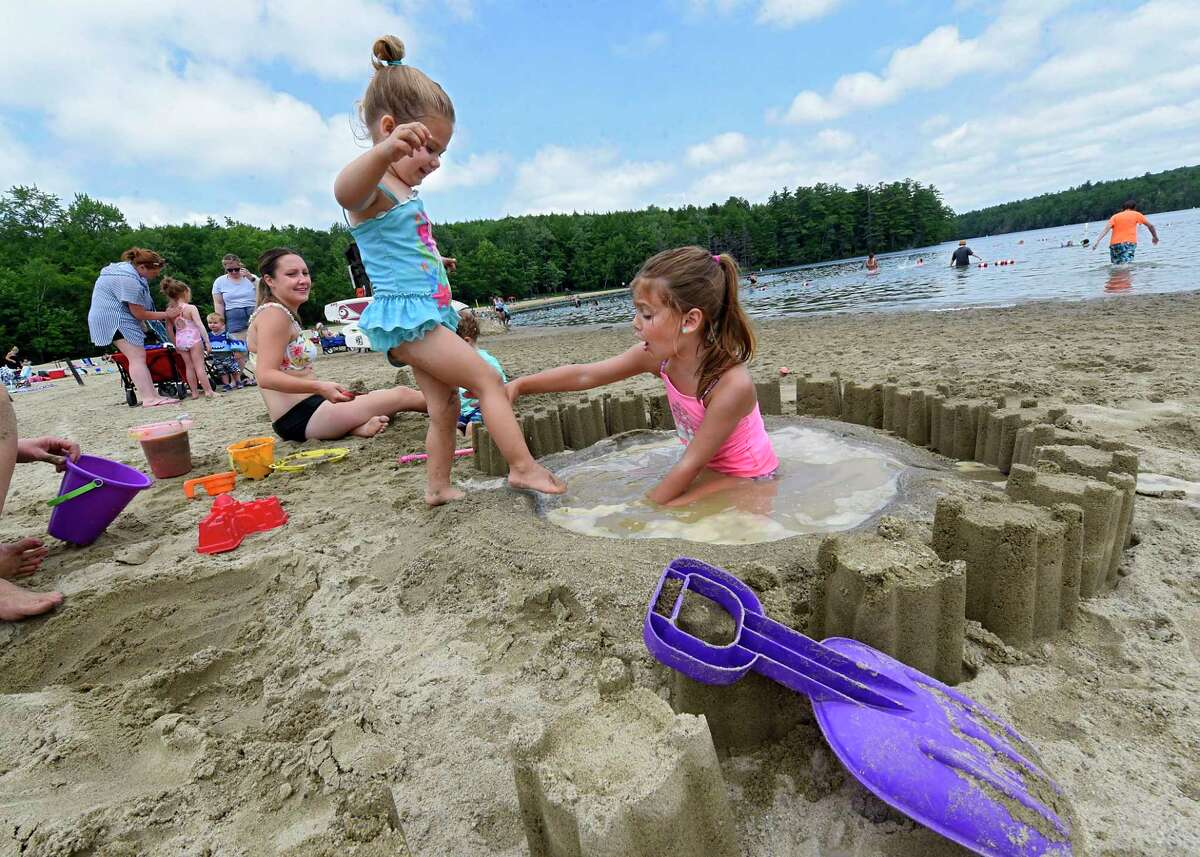 Audrey Tafilowski, 3, of Schodack is met with objection as she tries to step into the pool her sister Luciana, 5, right, made in the sand at Grafton Lakes State Park beach on Tuesday, July 7, 2020 in Grafton, N.Y. Their mother Meggan watches the contention at left. (Lori Van Buren/Times Union)