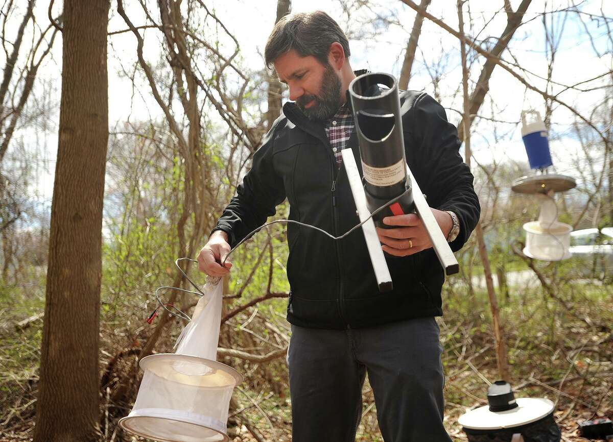 Scientist John Shepard, of the Connecticut Agricultural Experiment Station in New Haven, puts out a variety of mosquito traps on Land Conservation Trust property in Milford on April 18, 2018.