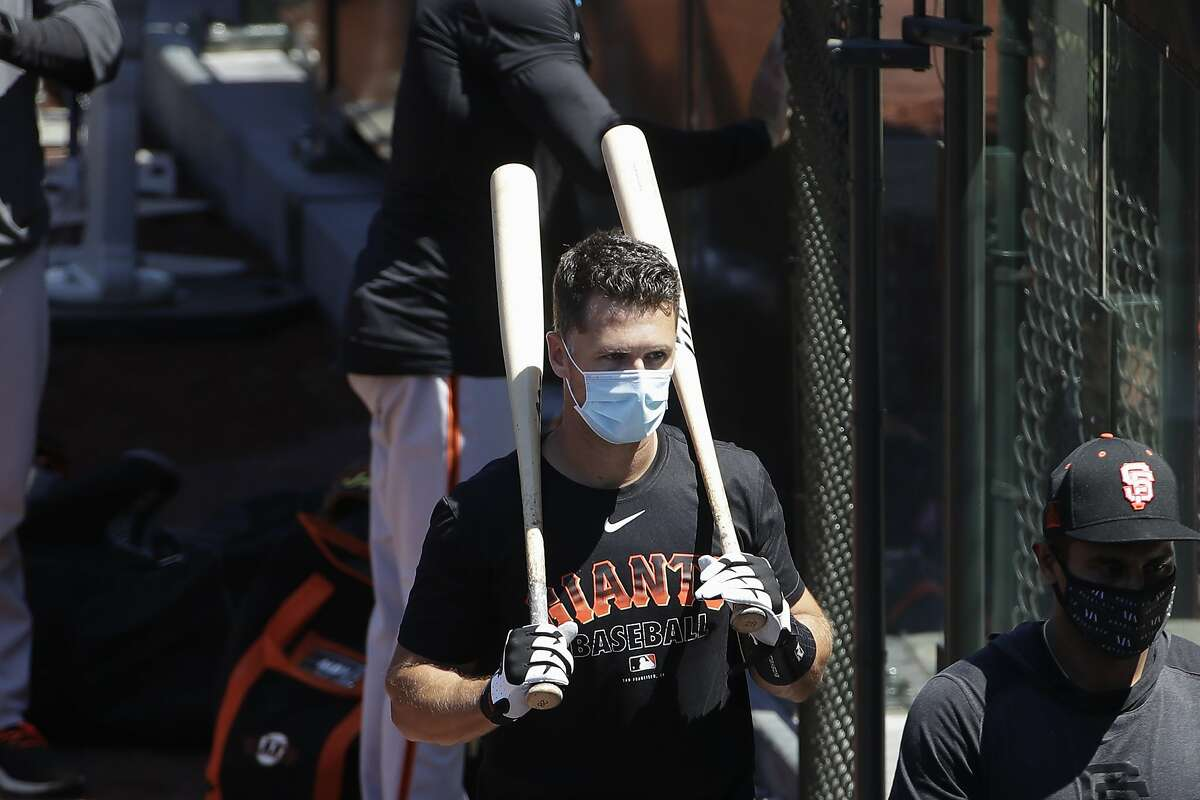 San Francisco Giants' Buster Posey carries his bats during a baseball practice in San Francisco, Sunday, July 5, 2020. (AP Photo/Jeff Chiu)