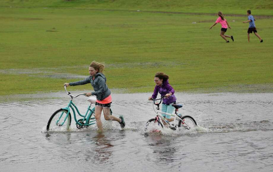 During a lull in rain from Hurricane Harvey in August 2017, Tori Covey and her sister Carley push bikes through the flooded Pearland baseball field. Many city residents could see discounts when they renew their flood insurance, reflecting the city's success in maintaining a Class 6 rating despite flood-rating requirements becoming more stringent in 2017. Photo: Steve Gonzales, Staff Photographer / Houston Chronicle / © 2017 Houston Chronicle