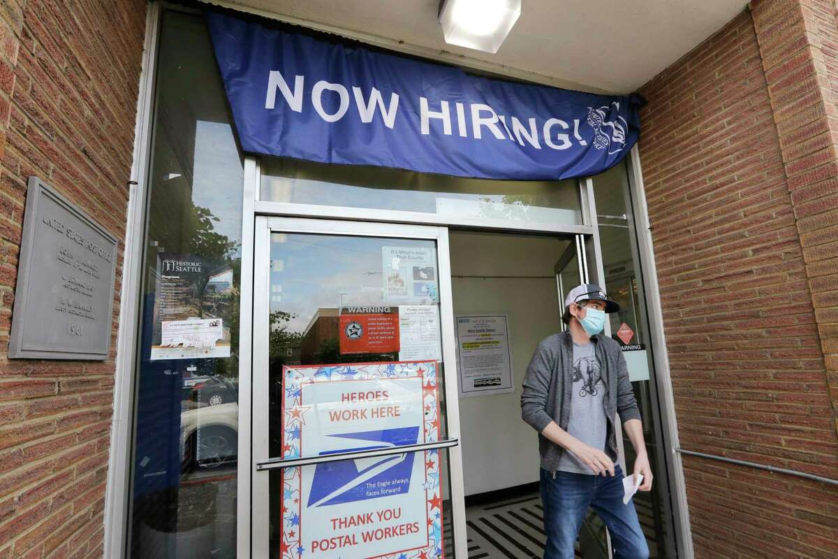 FILE - In this Thursday, June 4, 2020 file photo, a customer walks out of a U.S. Post Office branch and under a banner advertising a job opening, in Seattle. The job market took a big step toward healing in May 2020, though plenty of damage remains, as a record level of hiring followed record layoffs in March and April. The Labor Department reported Tuesday, July 7, 2020 that the number of available jobs rose sharply as well, but remained far below pre-pandemic levels. (AP Photo/Elaine Thompson, File)
