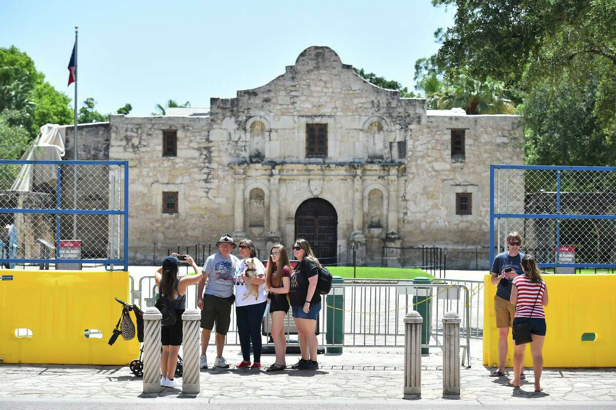 Visitors take pictures in front of the closed Alamo. Research shows that tourists want to