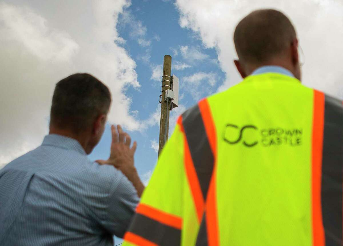 Brendan Carr (right), Commissioner of the Federal Communications Commission (FCC), looks at an existing small cell node capable of one day operating a 5G network with Crown Castle's Mike Kavanagh (left) east of downtown Houston along 69th Street, Monday, Sept. 30, 2019.