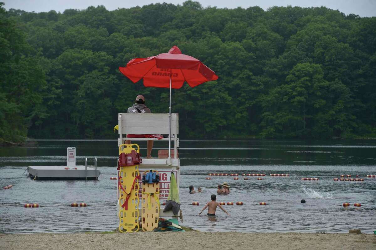 Head lifeguard Charlie Wilson of Easton, keeps an eye on swimmers at Topstone Park beach on Tuesday. The park and recreation department is loosening its reservation policy for residents looking to use the beach. Coronavirus restrictions are still in place. July 7, 2020, in Redding, Conn.