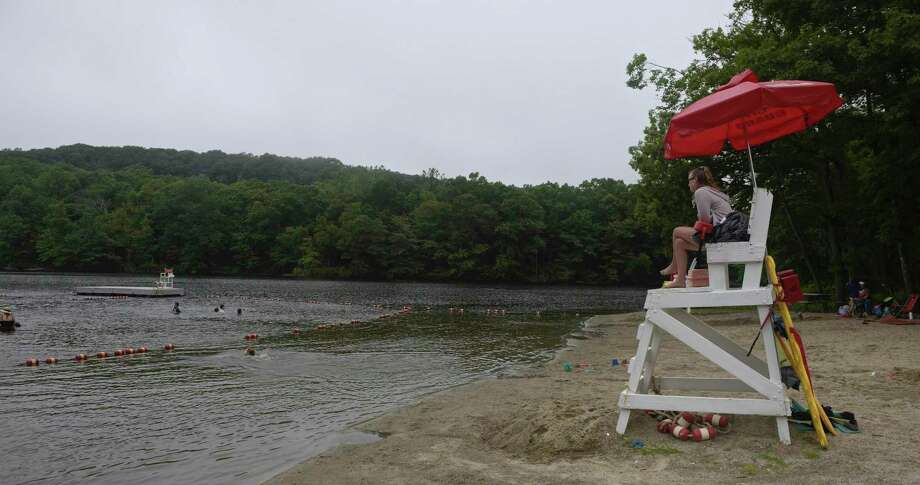 Lifeguard Ali Falder, of New Milford, keeps an eye on swimmers at Topstone Park beach on Tuesday. The park and recreation department is loosening its reservation policy for residents looking to use the beach. Coronavirus restrictions are still in place. July 7, 2020, in Redding, Conn. Photo: H John Voorhees III / Hearst Connecticut Media / The News-Times