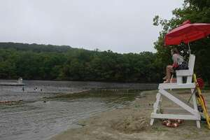 Lifeguard Ali Falder, of New Milford, keeps an eye on swimmers at Topstone Park beach on Tuesday. The park and recreation department is loosening its reservation policy for residents looking to use the beach. Coronavirus restrictions are still in place. July 7, 2020, in Redding, Conn.