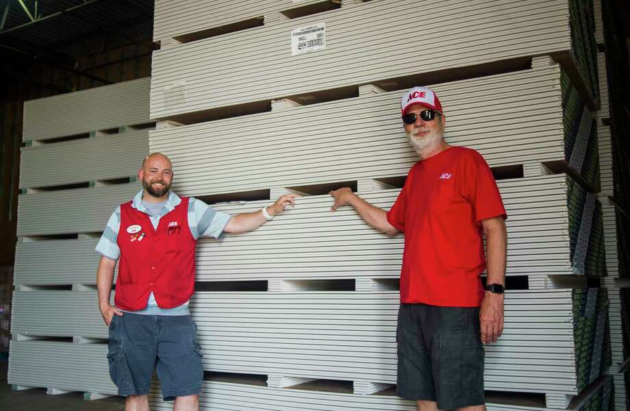 Daniel Buzzell, owner of Ace Hardware & Sports of Midland, left, and owner Greg White, right, stand in front of the 48,000 pounds of drywall which was donated to flood victims by Ace Hardware in partnership with USG Corporation, Tuesday inside J.E. Johnson's warehouse in Midland. From there, the United Way of Midland County will coordinate distribution to affected homes. (Katy Kildee/kkildee@mdn.net)