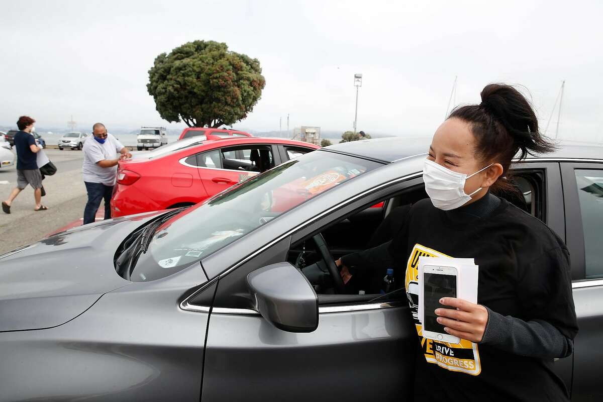 Saori Okawa, who drives for Uber, honks the horn of Rosa Mendoza's car as part of a drivers' protest caravan in San Francisco in June.