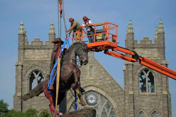 A crew attaches a harness to a crane as they prepare to remove the statue of Confederate Gen. J.E.B. Stuart on Monument Avenue in Richmond..