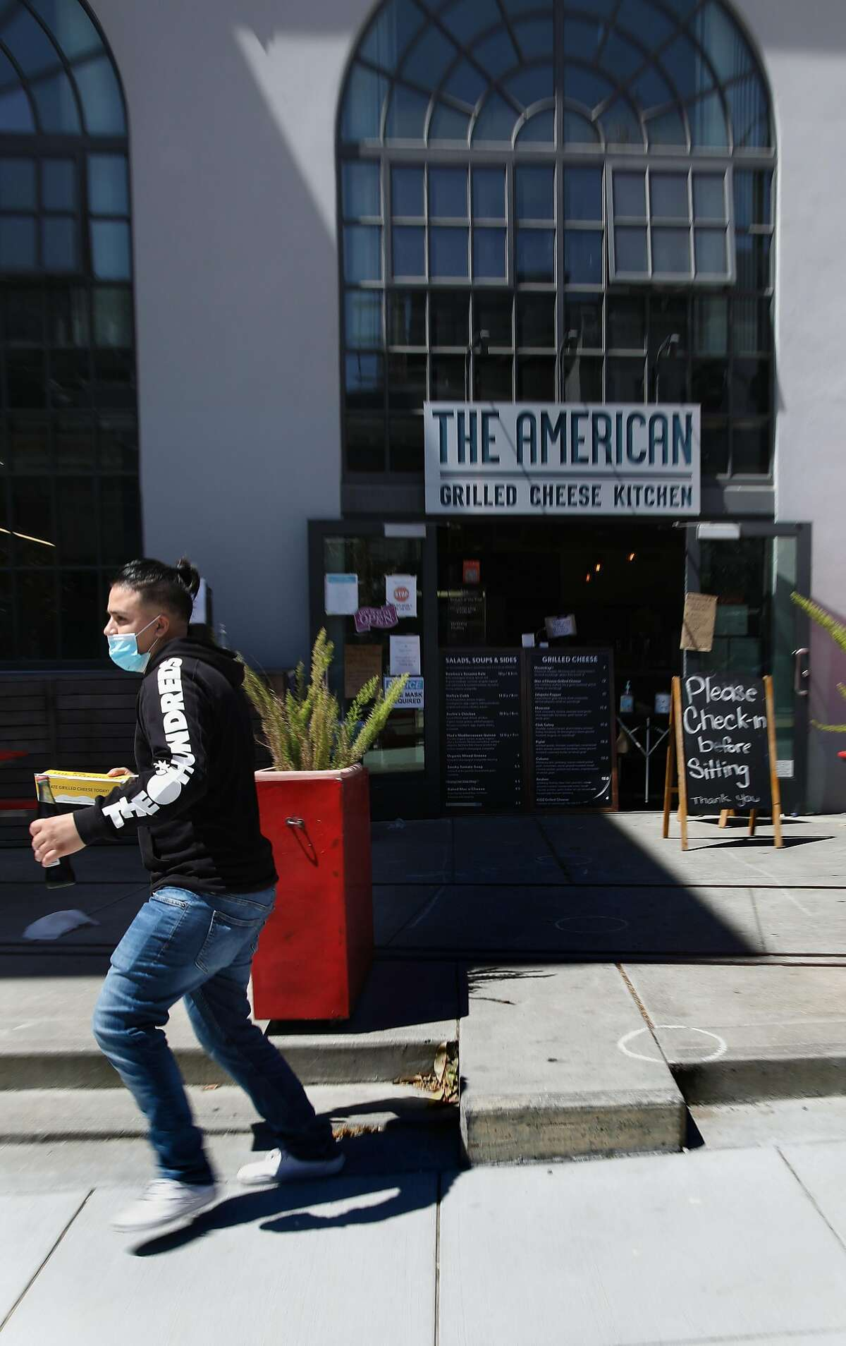 A customer picks up an order at The American Grilled Cheese Kitchen on Tuesday, July 7, 2020, in San Francisco, Calif. Mayor London Breed may announce a change of plans on indoor dining in SF.