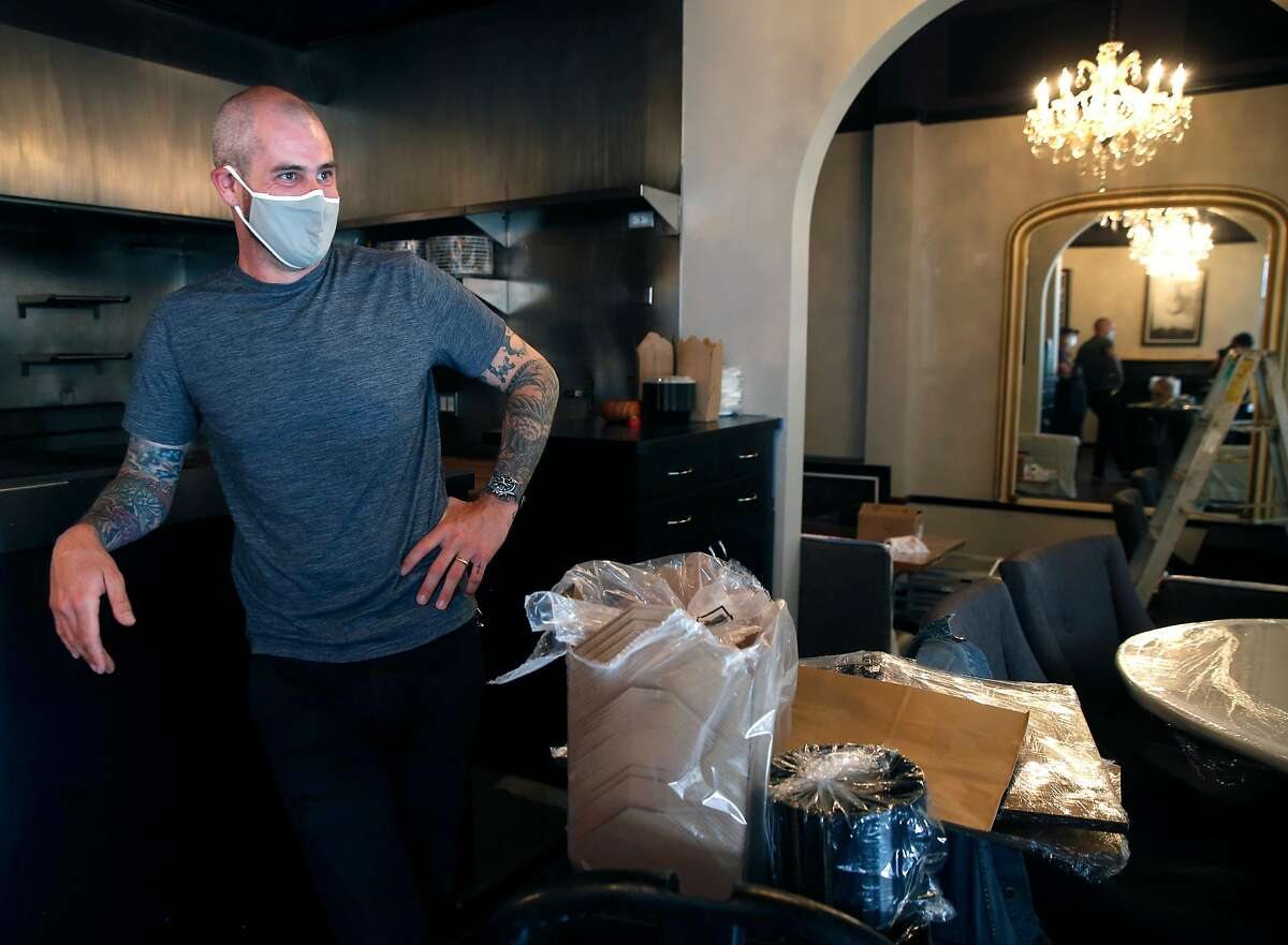 Sons & Daughters restaurant owner Teague Moriarity performs minor maintenance inside the small dining room in San Francisco, Calif. on Tuesday, July 7, 2020. Moriarity had been preparing to reopen on Bush Street before officials postponed plans to allow restaurants to resume indoor dining.