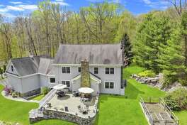 In the backyard there is a large raised paving stone patio and fenced vegetable garden.
