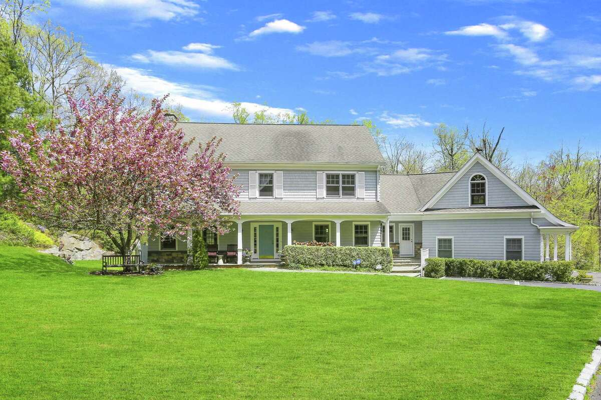 The gray colonial house at 12 Hunt Lane in Lower Weston sits on a 3.02-acre largely level property on a quiet cul-de-sac.