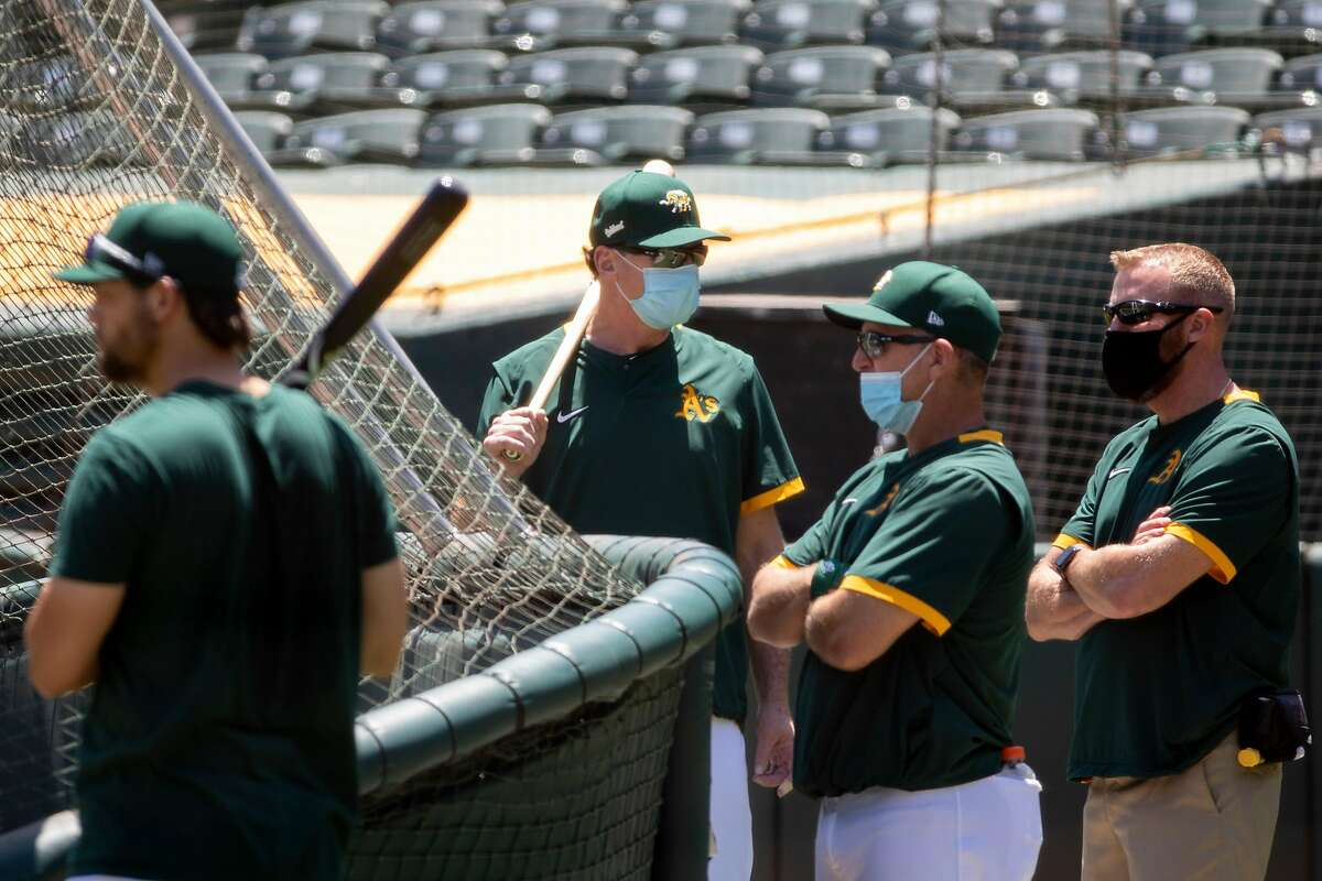 Various coaches sport face masks while participating in an Oakland A's training camp workout at O.Co Coliseum in Oakland, Calif. Tuesday, July 7, 2020. Due to COVID-19, the 2020 MLB season has been postponed with players just beginning to return for warmups and practices while wearing masks and keeping social distance.